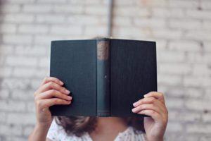 livre ouvert tenu tête caché